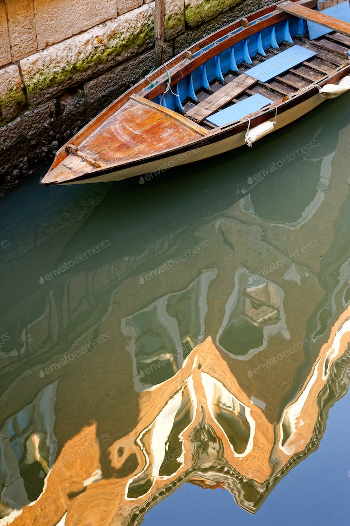 Old boat and old building reflection in water of venetian channel