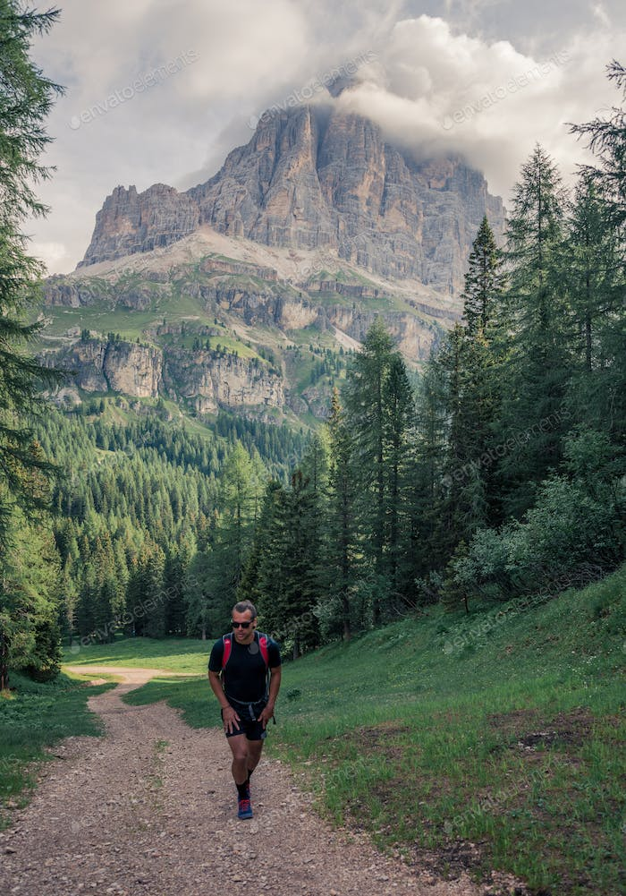 Male hiker trekking in the Dolomites mountains in Italy