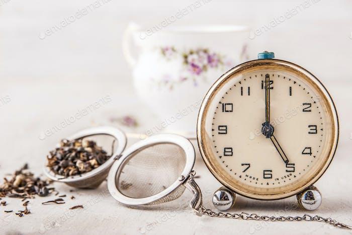 Vintage Wecker mit Teesieb auf dem weißen Tisch