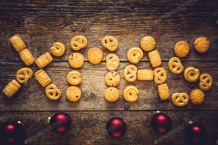 Weihnachtswort aus Lebkuchenplätzchen auf einem hölzernen Hintergrund. Weihnachtshintergrund