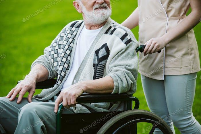 Nurse with patient on the wheelchair walking in the gardden