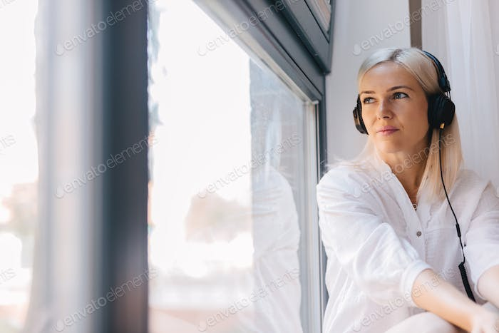 Woman listening to music, staring out the window.