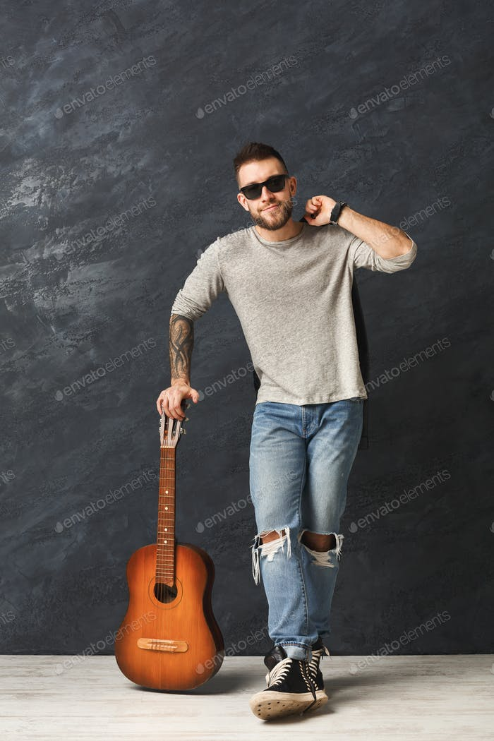 Handsome smiling man with guitar posing in studio