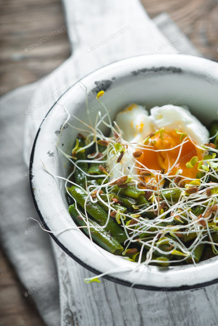Salad with beans, sprouted flax and quail eggs in a metal bowl