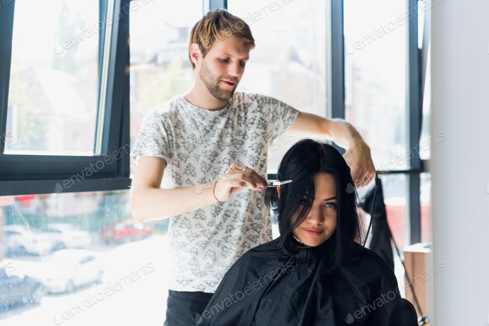 Confident young woman is looking at her reflection while hairdresser combing and cutting client&#39