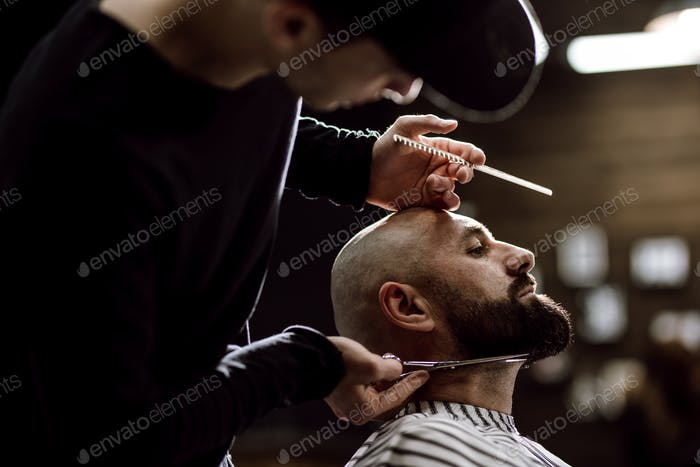 Fashion barber dressed in a black clothes tidies up men's beard  and scissors it in the