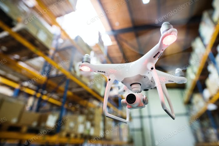 White drone flying inside the warehouse.