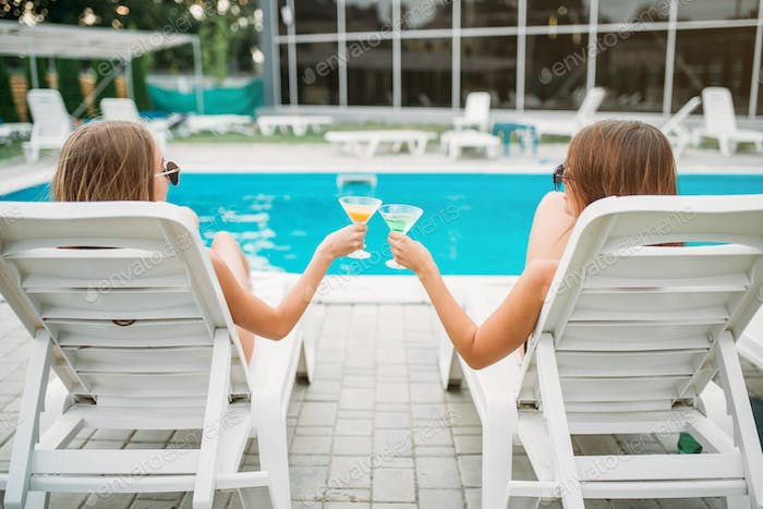 Two sexy girls lies on deck chairs near the pool
