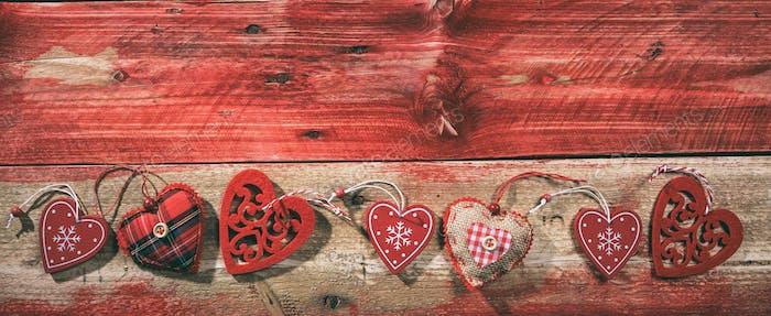 Dekorative Herzen auf rotem Holzhintergrund