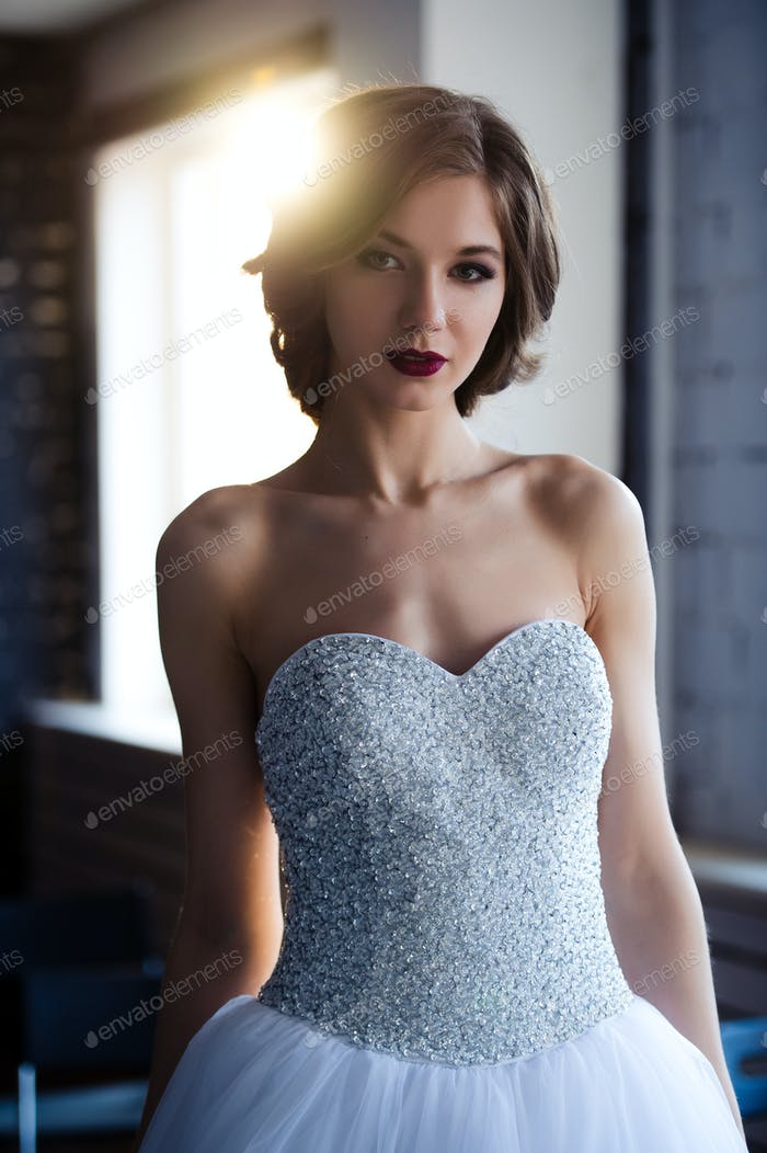 Attractive, beautiful girl in a stunning wedding dress indoors. Art photo in warm colors.