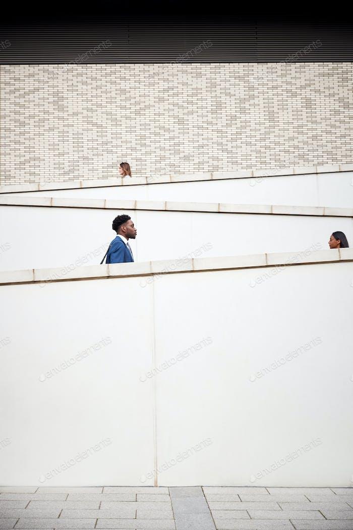 Fotografía gráfica de los viajeros caminando para Trabajo a lo largo de la pasarela de hormigón fuera del edificio