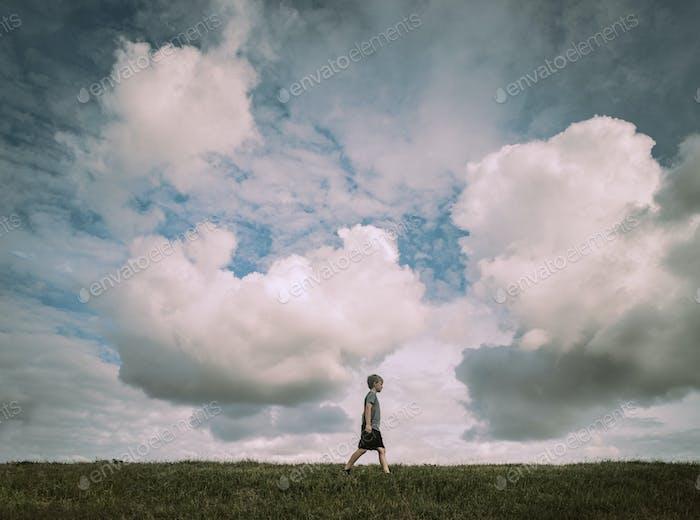 Boy Walking Across a Hill