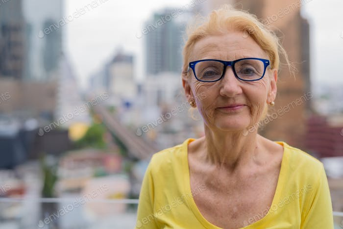 Beautiful senior woman with eyeglasses in city