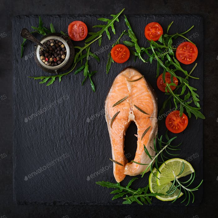 Cooked on steam salmon steak with vegetables on black background.