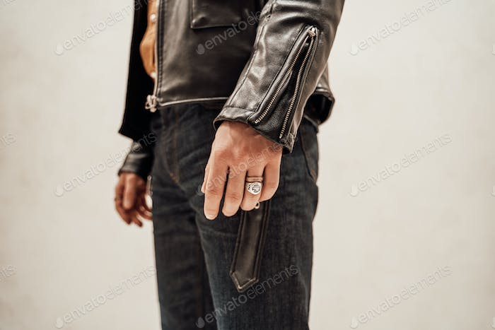 Close-up photo of the male hand with two rings and leather coat on the white background