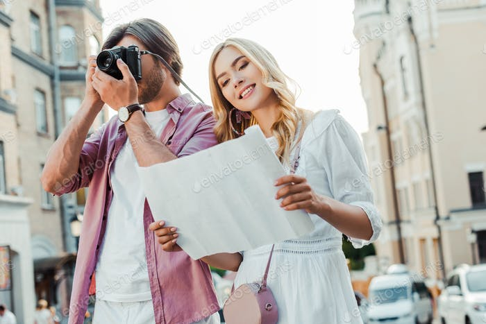 portrait of tourists with map and photo camera on city street