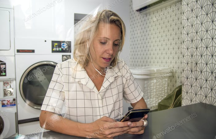 Caucasian woman waiting at the self service laundryomat