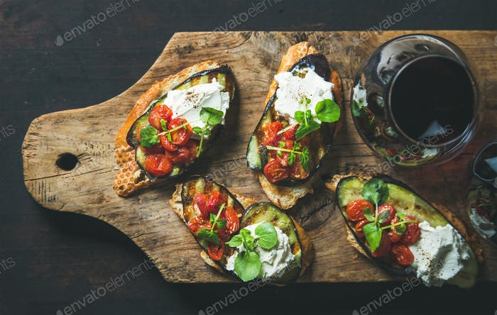 Glass of red wine, brushetta with vegetables, cream-cheese, arugula
