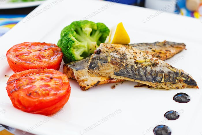Mackerel fillets (fish) on a grill with vegetables