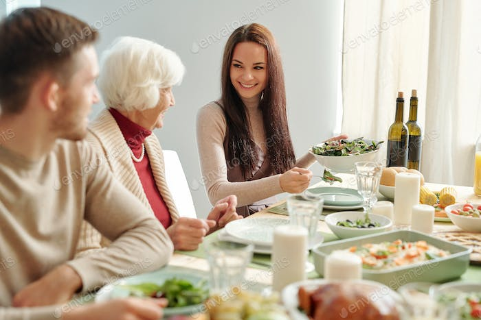 Smiling young woman putting salad on plate of grandma while looking at her