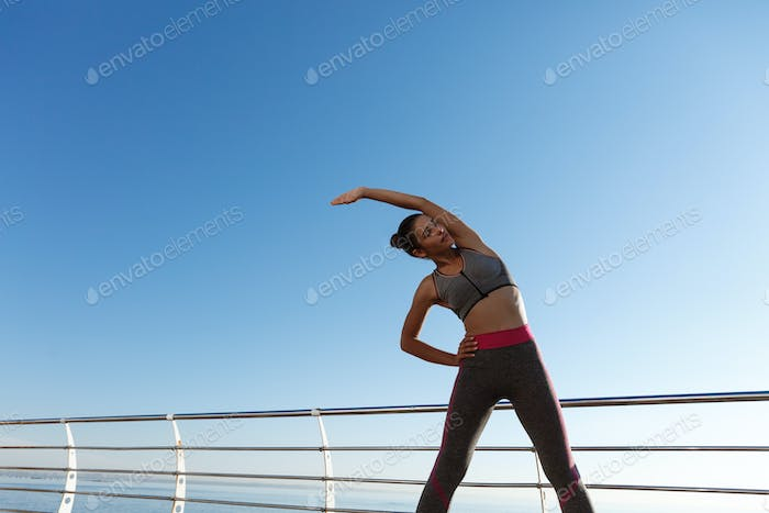Image of attractive healthy woman stretching and training on a pier. Girl having workout on fresh