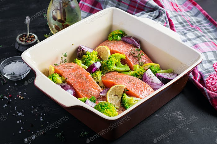 Salmon, broccoli and red onion slices are prepared in a baking dish.