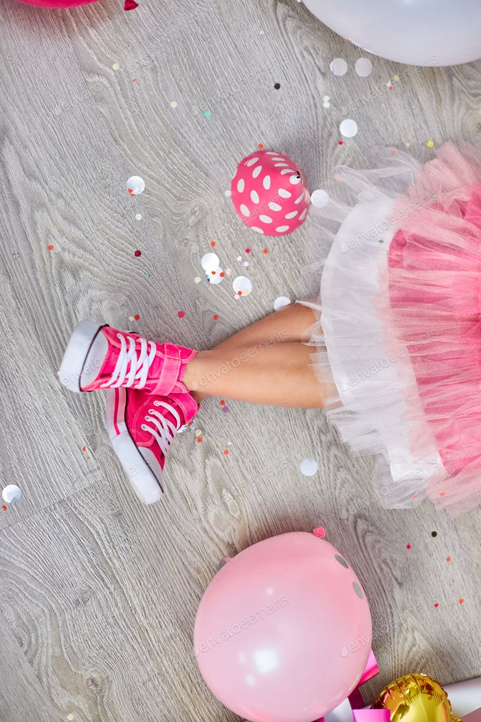 Creative lay out of funky leg of girl in pink sneakers and dress, flat lay