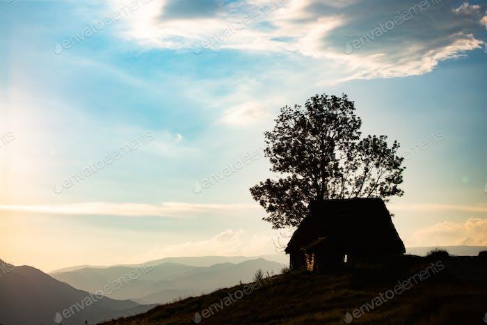 Sonnenuntergang Szene mit Hütten-Silhouette