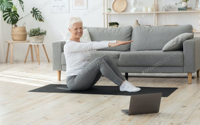 Online Training. Sporty Senior Woman Exercising In Front Of Laptop At Home