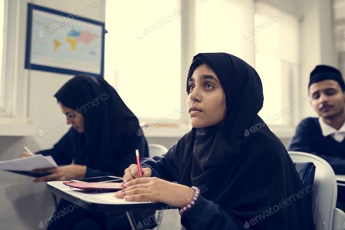 diverse muslim children studying in classroom