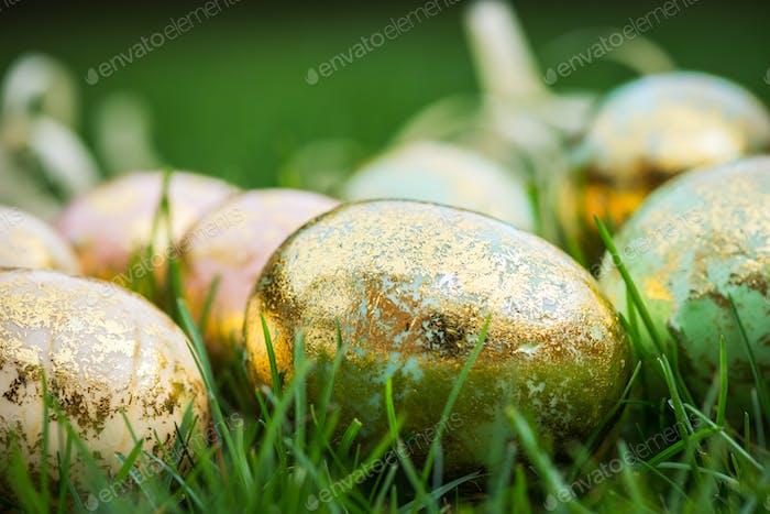 Golden Easter Eggs on green Grass Background