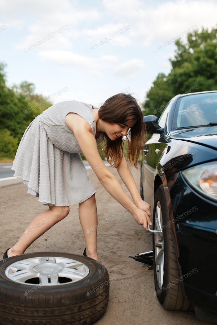 Autopannung, junge Frau legt den Ersatzreifen