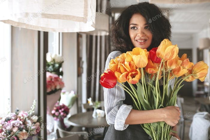 Pretty smiling girl with dark curly hair looking aside with bouquet of tulips in hands