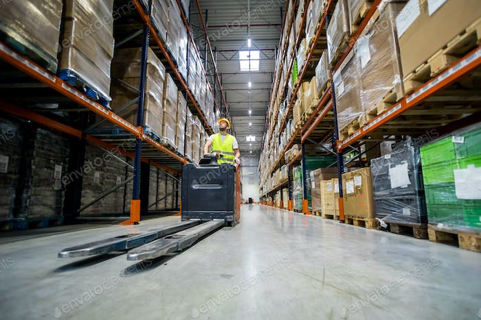 Forklift operator during work in large warehouse drives between shelves