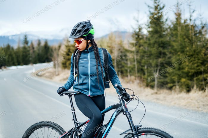 Female mountain biker standing on road outdoors in winter nature.