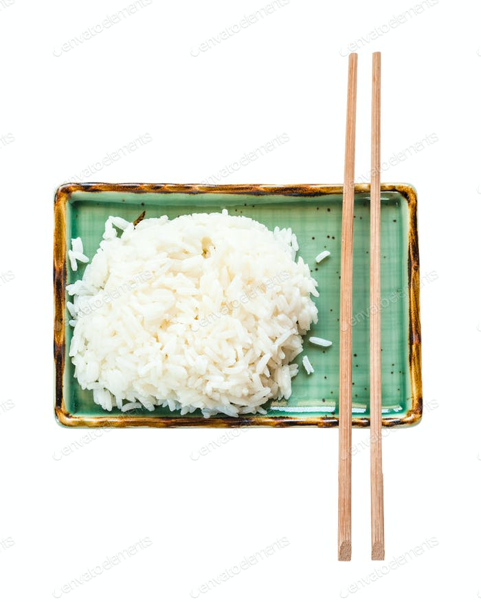 boiled rice and chopsticks on green plate isolated