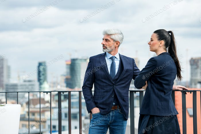 A businessman and businesswoman standing on a terrace, talking.