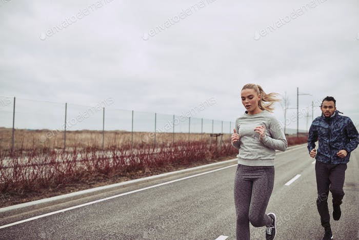 Diverse young couple in sportswear jogging along a country road