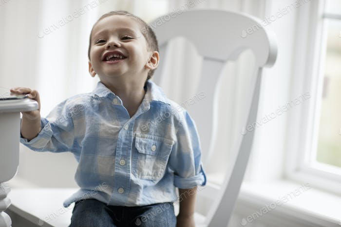 A young boy sitting on a chair, smiling and looking up.