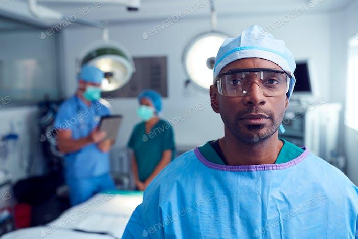 Porträt von männlichen Chirurgen tragen Peelings und Schutzbrille in Krankenhaus Operating Theater
