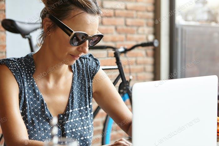 Half profile of stylish woman freelancer wearing sunglasses working remotely on modern laptop pc, ha