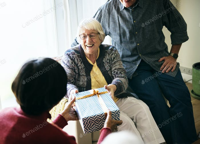 Cheerful senior woman recieving a gift box