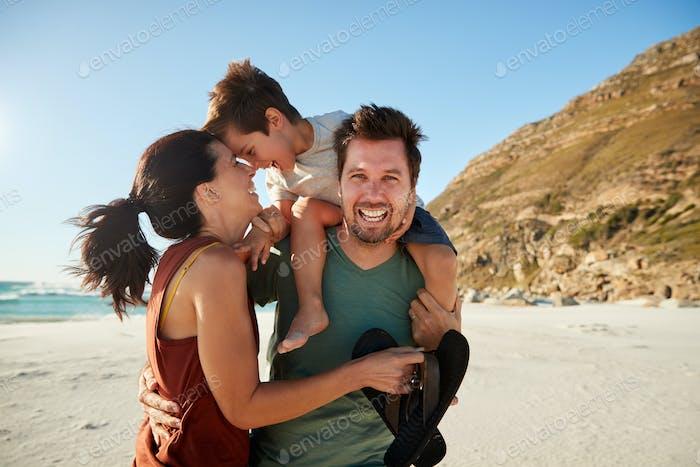 Mediados adultos pareja blanca de pie en una Playa, papá llevando hijo en sus hombros, vista frontal, de cerca