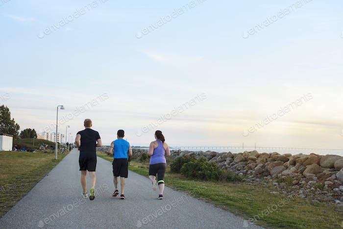 Friends running on footpath