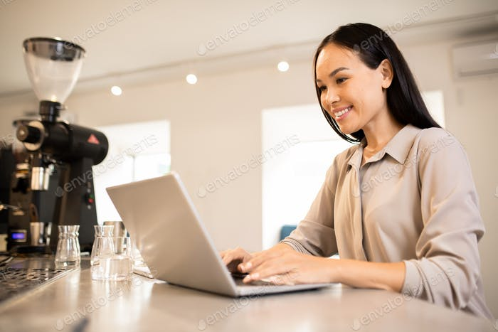 Young happy female entrepreneur sitting by workplace in front of laptop