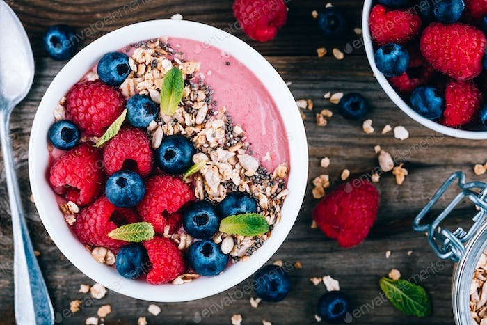 Acai smoothie and granola bowl with fresh raspberries and blueberries