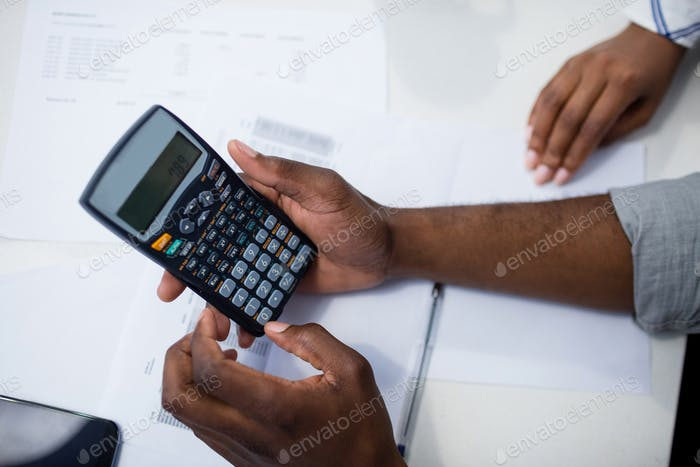 Hands of man using a calculator