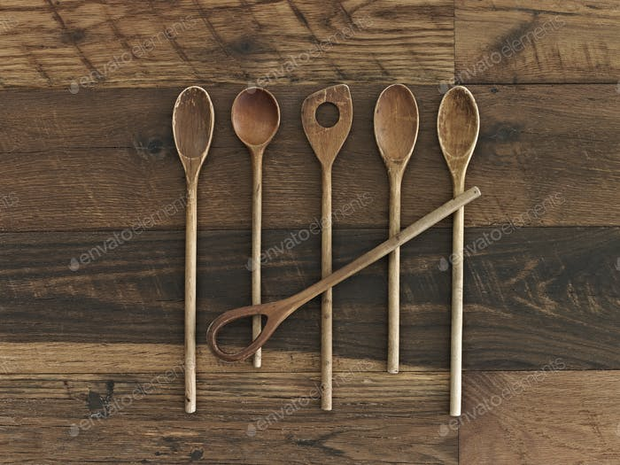 An arrangement of six wooden spoons of a variety of shapes and sizes on a wooden table.
