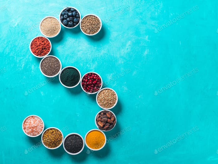 S letter of superfoods in bowl on blue background