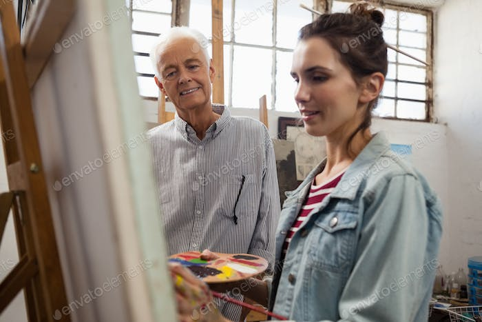 Senior man watching while artist painting on canvas
